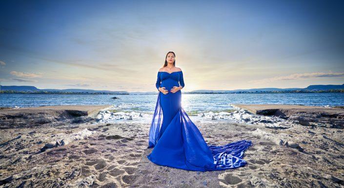 gravid-kvinde-strand-huk-oslo-blå-kjole-holder-baby-magen-står-centreret