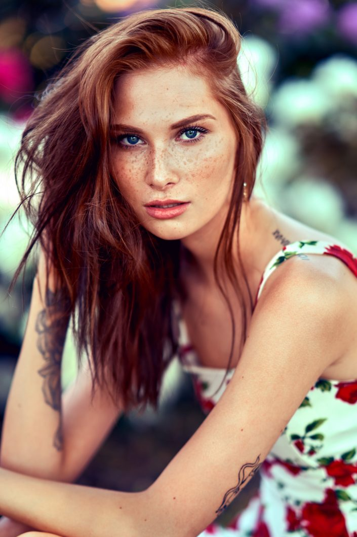 kvinde-vakker-rødt-hår-blå-øjne-fregner-foran-blomster